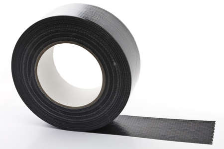 black adhesive tape  on light background. partly unroled