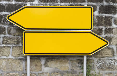 direction signs with wall in background. yellow signs. arrow shape