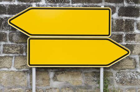 flecha derecha: se�ales de direcci�n con la pared de fondo. se�ales amarillas. flecha forma Foto de archivo