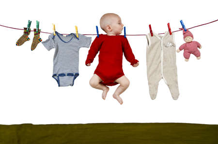 young child hanging at clothes line together with toys and clothing