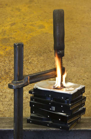 bulk memory: clamp pressing on burning stack of hard drives in rusty background
