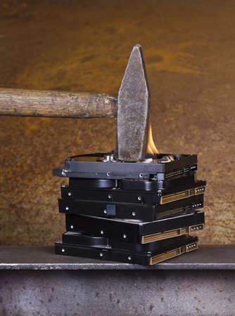 mass storage: hammer on burning hard disk in rusty background