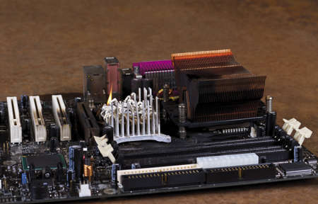 main board: molten cooling element on computer main board. Rusty background Stock Photo