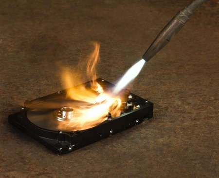 blowpipe: burning a hard disk drive with a welding torch in rusty background Stock Photo