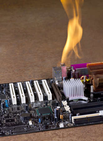 annihilate: burning computer mainboard in rusty background Stock Photo