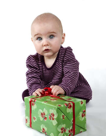 young child holding huge present and looking towards the camera Stock Photo - 11111045