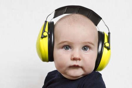 시끄러운 환경에서 노란 귀 보호 아기. 중간 회색 배경