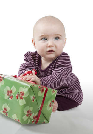 interrogative: young baby sitting and holding gift looking alienated