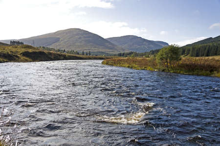 runnel: blue river in the heart of scotland with mountains in background