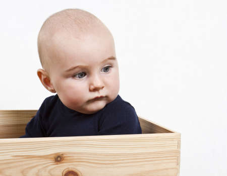 nursling: single toddler with dark shirt in wooden box looking to the right. Stock Photo