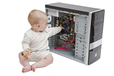 screwdriver: young child with screwdriver in hand working on open computer in white background.