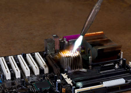 overheating: overheating a heat sink on a computer board with a welding torch in rusty background Stock Photo