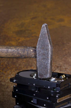 fixed disk: hammer on stack of hard disk in rusty background