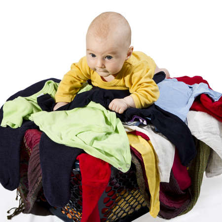 young child on many clothes in clothesbasket isolated on white background photo