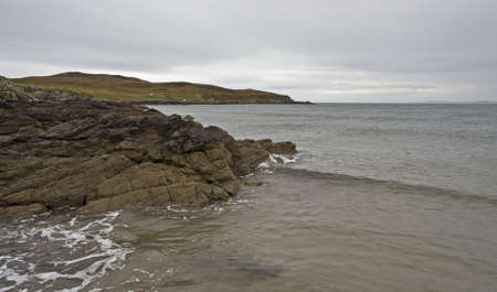 stoney: stoney coastline in scotland with small hill in background Stock Photo