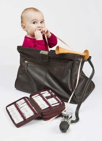 Kind sitzt in Hebammen Fall mit homöopathischen Kügelchen, Hörrohr und Maßband. Keine Produktnamen, nur gewöhnliche Namen der homöopathischen Medizin. Lizenzfreie Bilder