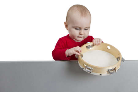 young child holding tambourine behind grey shield. isolate on white background Stock Photo - 11772638