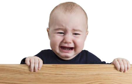 crying young child holding board. isolate on white background photo
