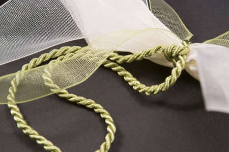 fluting: studio photography  of a decorative bow with green cord in dark back