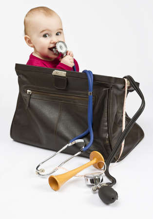 toddler in midwifes case with ear trumpet and measuring tape