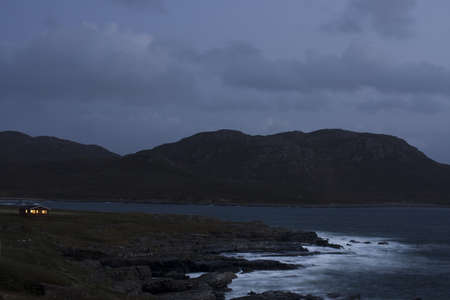 afield: scottish coast at night with light in single house