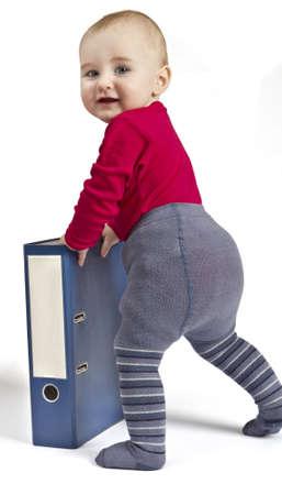 niño pequeño en la camisa roja de pie junto a carpetas de anillas de color azul. de fondo blanco con la sombra. Mirando hacia la cámara Foto de archivo - 11881375