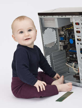 young child in blue shirt with open computer on neutral background photo