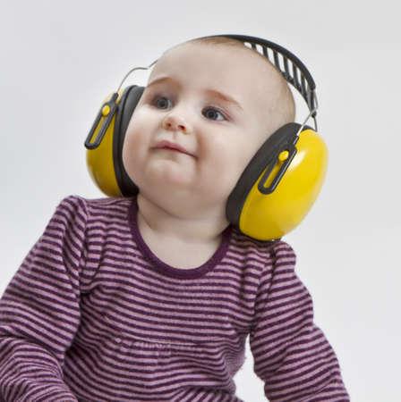 contaminacion acustica: beb� con protecci�n para los o�dos de color amarillo en el medio ambiente ruidoso. fondo gris neutro