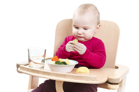 highchair: young child in red shirt eating vegetables in wooden high chair.