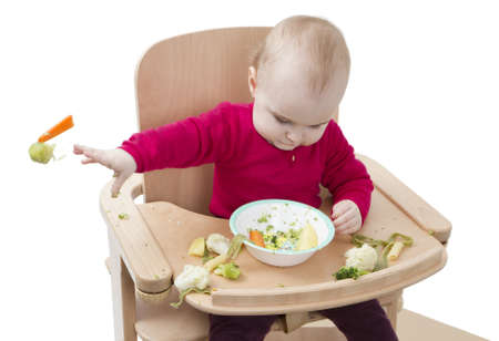 young child in red shirt eating vegetables in wooden chair  Stock Photo - 12499526