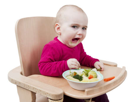 young child in red shirt eating vegetables in wooden chair Stock Photo - 12499536