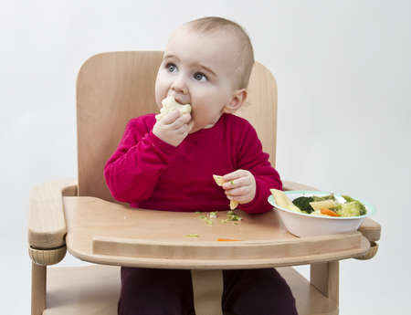 nursling: young child in red shirt eating vegetables in wooden chair  Stock Photo