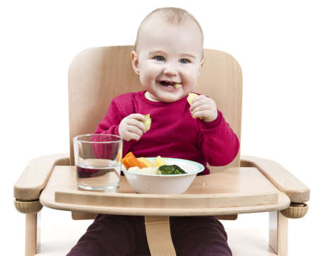 young child in red shirt eating vegetables in wooden chair  Standard-Bild