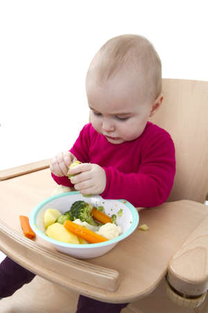 young child in red shirt eating vegetables in wooden chair Stock Photo - 12499564