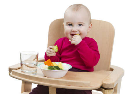 young child in red shirt eating vegetables in wooden chair  Stock Photo