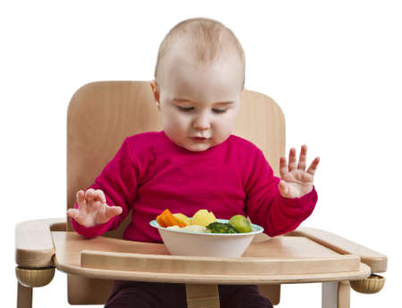 highchair: young child in red shirt eating vegetables in wooden chair  Stock Photo