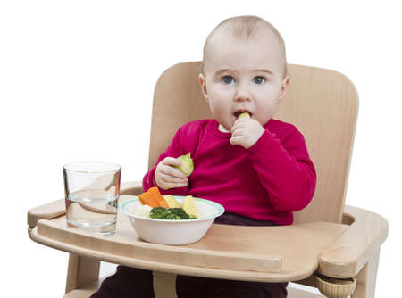 young child in red shirt eating vegetables in wooden chair  Stock Photo - 12802587
