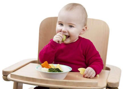 young child in red shirt eating vegetables in wooden chair Stock Photo - 12802607