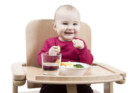 young child in red shirt eating vegetables in wooden chair Stock Photo - 12802628