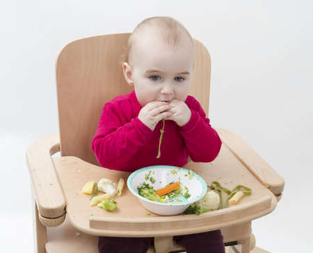 young child in red shirt eating vegetables in wooden chair Stock Photo - 12793530