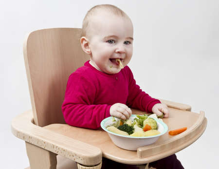 young child in red shirt eating vegetables in wooden chair  Stock Photo - 12802644
