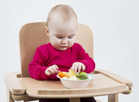 young child in red shirt eating vegetables in wooden chair Stock Photo - 12802656