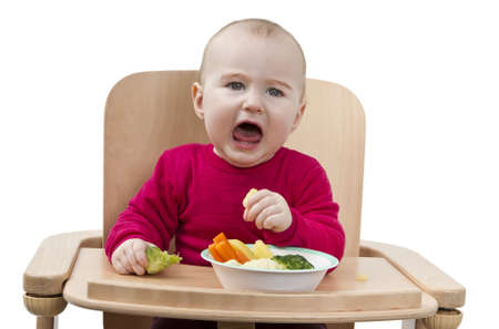 young child in red shirt eating vegetables in wooden chair Stock Photo - 12802654