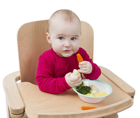 young child in red shirt eating vegetables in wooden chair Stock Photo - 12802663