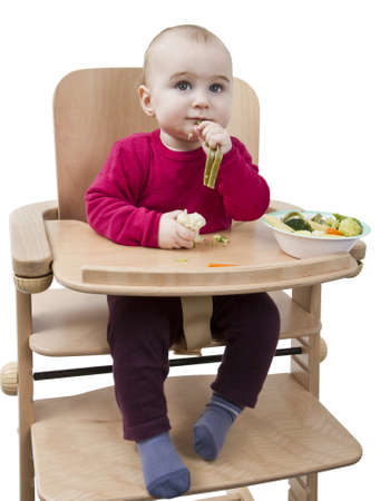 young child in red shirt eating vegetables in wooden chair  Stock Photo - 12802674