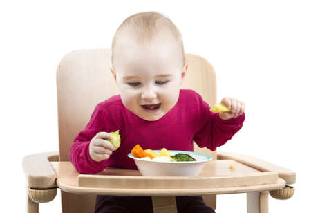disclaim: young child in red shirt eating vegetables in wooden chair  Stock Photo