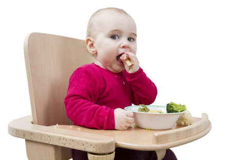 ailment: young child in red shirt eating vegetables in wooden chair  Stock Photo