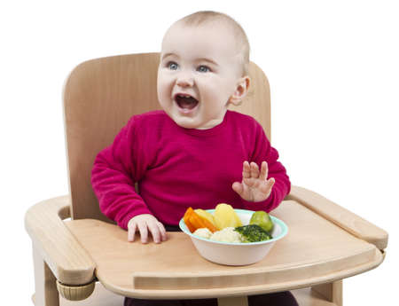 young child in red shirt eating vegetables in wooden chair Stock Photo - 12932677
