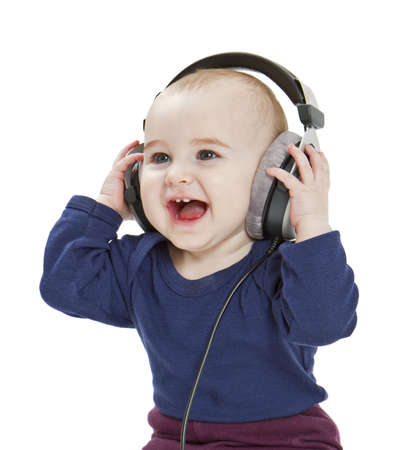 young, happy child with earphones listening to music  isolated on white background Stock Photo