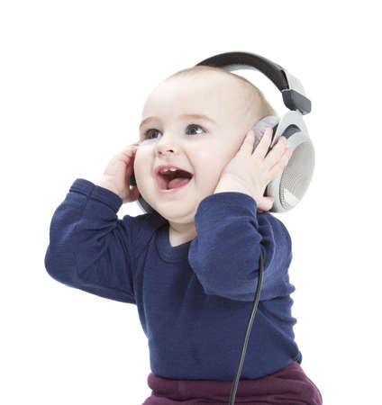 niño cantando: niño pequeño con los auriculares escuchando música aislado en fondo blanco Foto de archivo